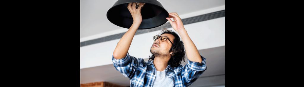 Man changing lightbulb for eco-friendly alternative