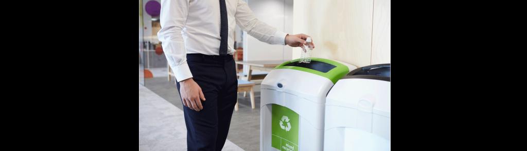 Man in suit recycling plastic bottle in office recycling bins