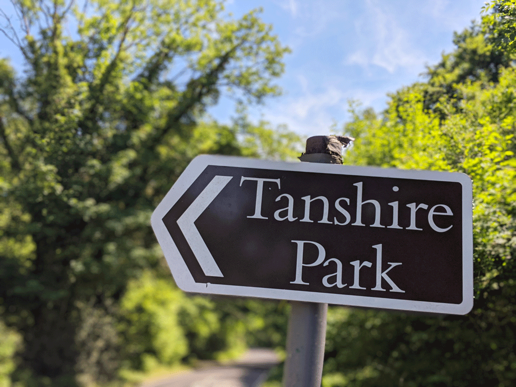 Brown sign in Surrey countryside points to Tanshire Park business park