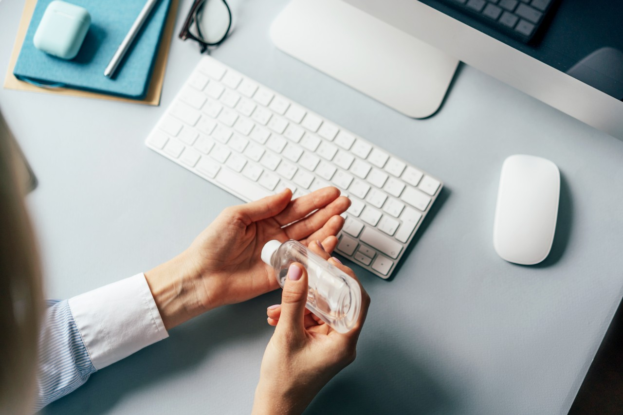 Employee using antibacterial hand sanitiser while she works